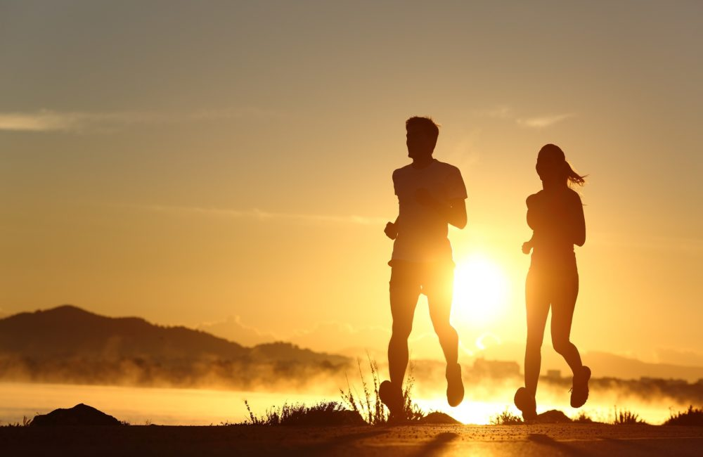 Silhouette of a couple running at sunset with the sun in the background